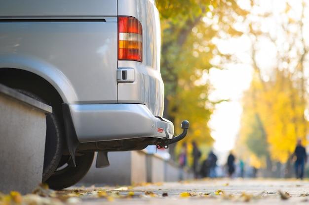 Van garé sur une rue de la ville par une belle journée d'automne avec des gens flous marchant sur la zone piétonne.