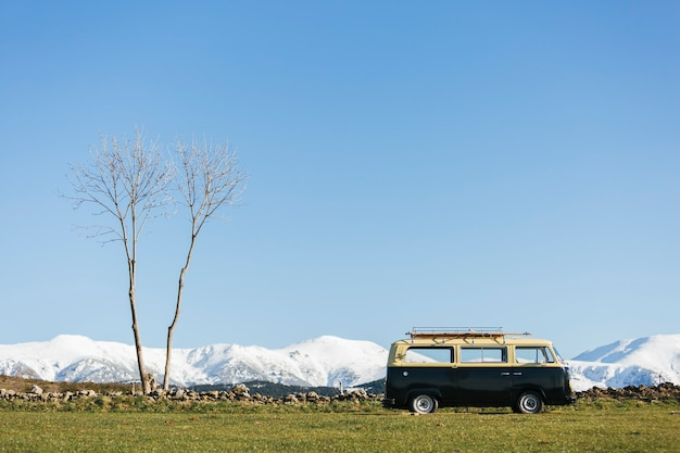 Van noir sur un champ vert avec des montagnes enneigées à l'arrière