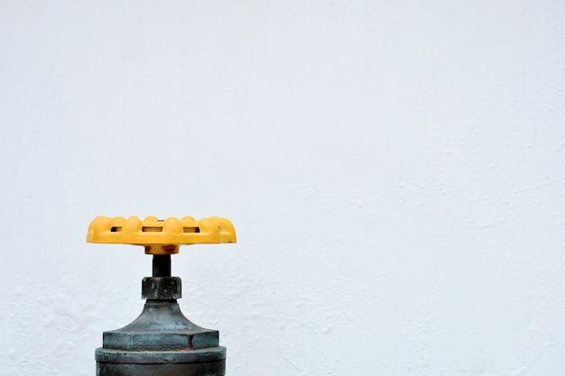 Vanne d'eau jaune devant le mur blanc.
