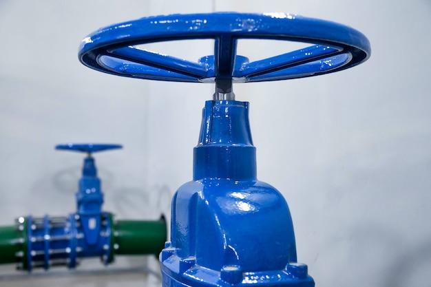 La vanne de fermeture de la station de pompage est un pipeline avec des réservoirs d'eau dans une salle industrielle pour l'approvisionnement en eau à haute pression. tuyaux d'arrosage d'eau et système de contrôle de la pression. espace de copie pour le site