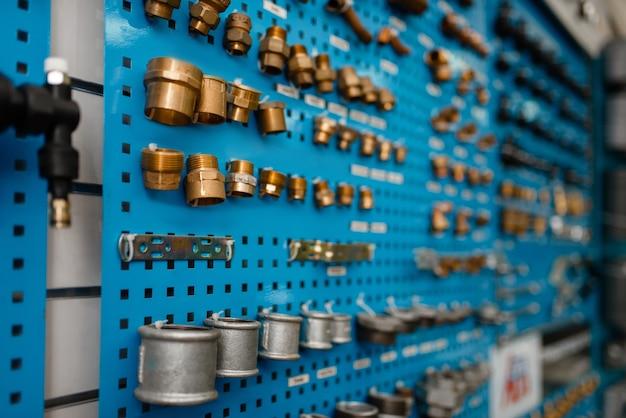 Vannes d'eau et adaptateurs de tuyaux sur vitrine, magasin de plomberie. atelier d'ingénierie sanitaire professionnel, personne, technologie de plomberie moderne