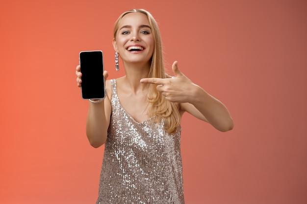 Vantard fier charmant femme blonde élégante en robe de soirée élégante montrer l'affichage du smartphone pointant fièrement l'écran du téléphone mobile souriant montrant le petit ami photo, debout sur fond rouge.