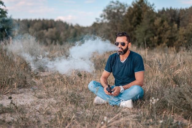Vaper barbu élégant à l'air frais fumant un appareil à fumée électronique. vapoter.