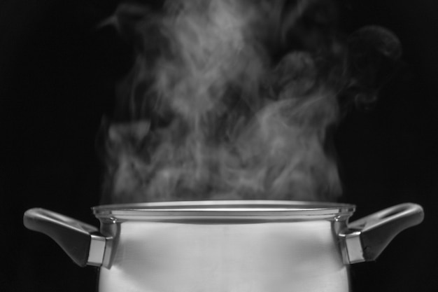 Vapeur sur marmite dans la cuisine sur fond sombre