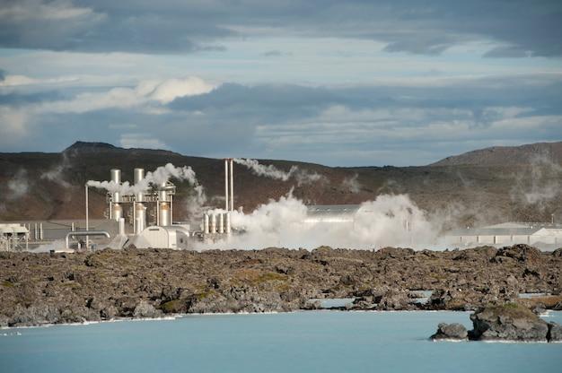 Vapeur sortant d'une centrale géothermique au-dessus d'un littoral de lac rocheux
