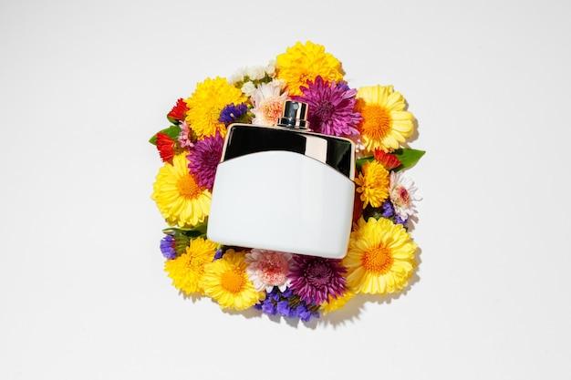 Vaporisateur de parfum et petites fleurs sur mur gris se bouchent