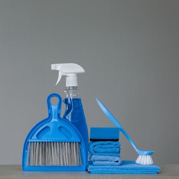Vaporisez du détergent, une brosse à vaisselle, des chiffons à poussière, une éponge, une cuillère et un balai. espace de copie.