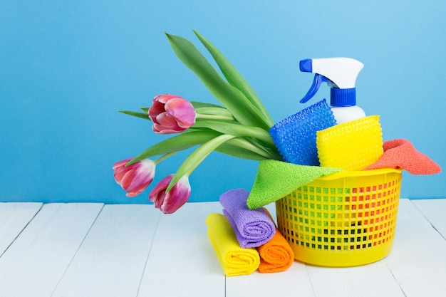 Vaporisez avec du détergent, des éponges de nettoyage, des chiffons et des fleurs de printemps dans le panier