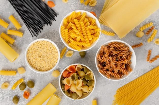 Variation de pâtes sèches dans des bols blancs sur fond de béton gris. fond de cuisine italienne. vue de dessus. copiez l'espace.