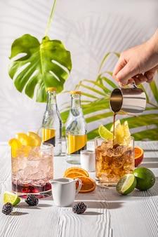 Variations de boisson rafraîchissante espresso-tonic avec différents fruits et sirops sur une table en bois sous le soleil du matin