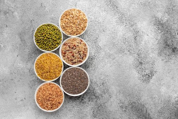 Variations de porridges et de haricots dans des soucoupes blanches sur un fond de béton gris