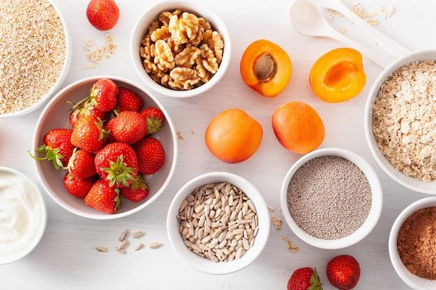 Variaty de céréales brutes, fruits et noix pour le petit déjeuner. flocons d'avoine et coupe en acier, orge, noix, chia, abricot, fraise. ingrédients sains