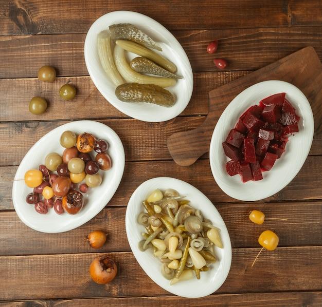Variété d'apéritifs, sélections d'aliments marinés dans des assiettes blanches