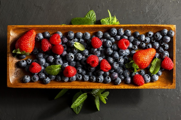 Variété appétissante de fruits des bois fraises grosses fraises framboises bleuets baies rouges sur un plateau en bois et feuilles de menthe menthe poivrée sur une surface sombre texturée vue de dessus avec copie s