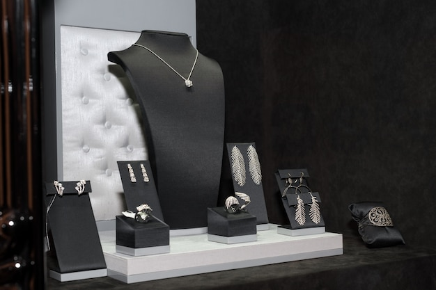 Variété de bijoux en vitrine. vente de bagues, bracelets, boucles d'oreilles et colliers sur des supports.