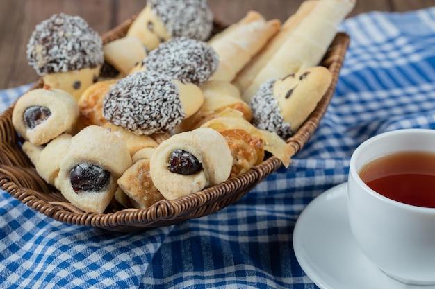 Variété de biscuits dans le plateau avec une tasse de thé de côté.