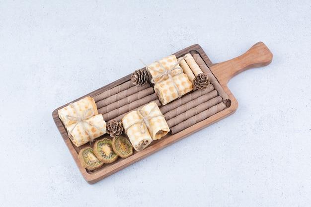 Variété de biscuits et kiwi séchés sur planche de bois.