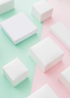 Variété de boîtes blanches sur fond de papier rose et vert