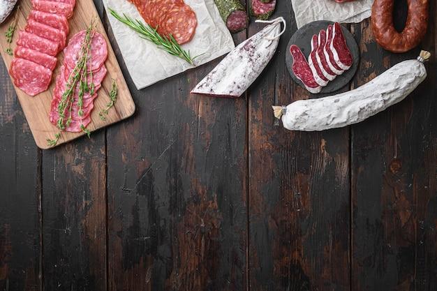 Variété de chorizo séché à sec, de fuet et d'autres saucisses coupées en tranches avec des herbes sur fond de bois foncé, vue de dessus avec un espace pour le texte.