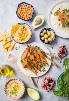 Variété de collations végétaliennes saines, trempettes gastronomiques. houmous, carottes rôties, riz au tempeh dans des bols en céramique vu de dessus, aliments à base de plantes