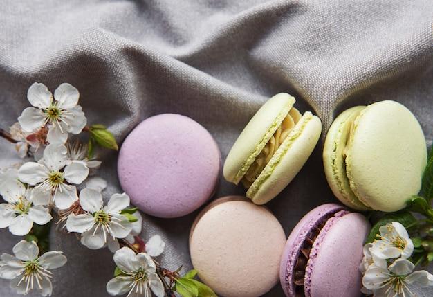 Variété colorée de macarons sucrés français sur fond textile gris avec fleur de printemps