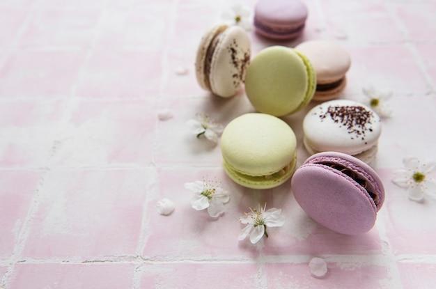 Variété colorée de macarons sucrés français sur un fond de tuile rose avec des fleurs de printemps
