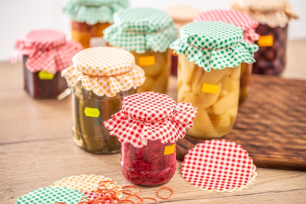 Variété de cornichons et de conserves faits maison, dessus à carreaux et étiquettes jaunes sur les pots.