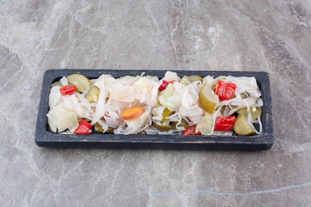 Variété de cornichons hachés sur assiette sombre.