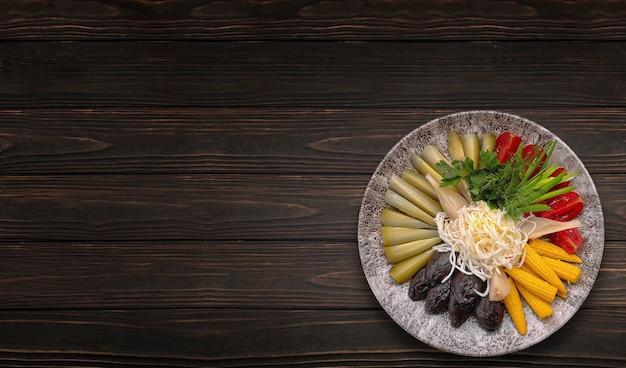 Une variété de cornichons de légumes sur plaque cadre horizontal sur table en bois foncé