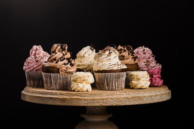 Variété de cupcakes sur le plat en bois sur fond noir