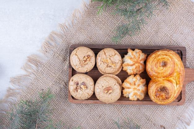Variété de délicieux cookies sur planche de bois.