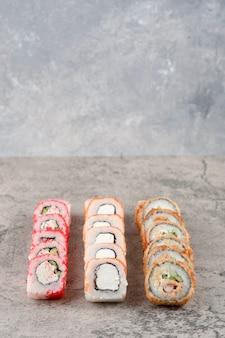 Variété de délicieux rouleaux de sushi placés sur fond de marbre