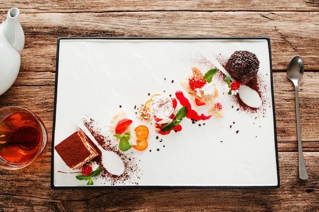 Variété de desserts sucrés avec thé et cuillère