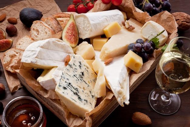 Variété de différents fromages avec du vin, des fruits et des noix.