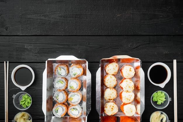 Variété de différents sushis et petits pains, saumon et thon dans l'ensemble de concept de livraison de nourriture, sur table en bois noir