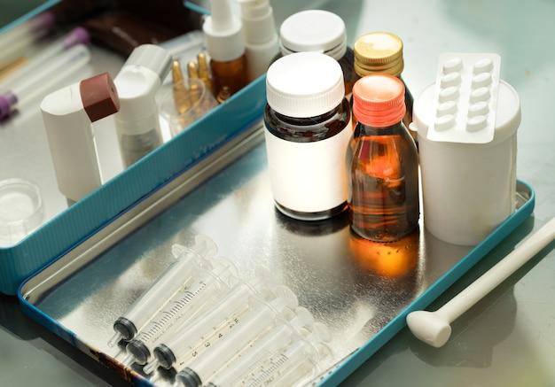 La variété d'emballages de médicaments sur le tacle comprend une seringue de sirop mdi en vaporisateur sur fond flou