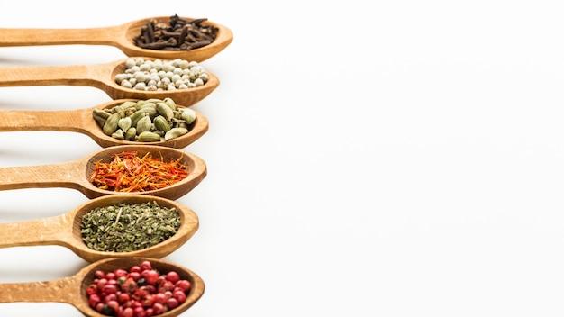Variété d'épices dans des cuillères en bois avec copie-espace