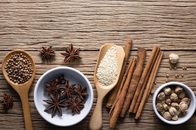 Une variété d'épices et d'herbes naturelles complète les aliments santé sur une table rustique.