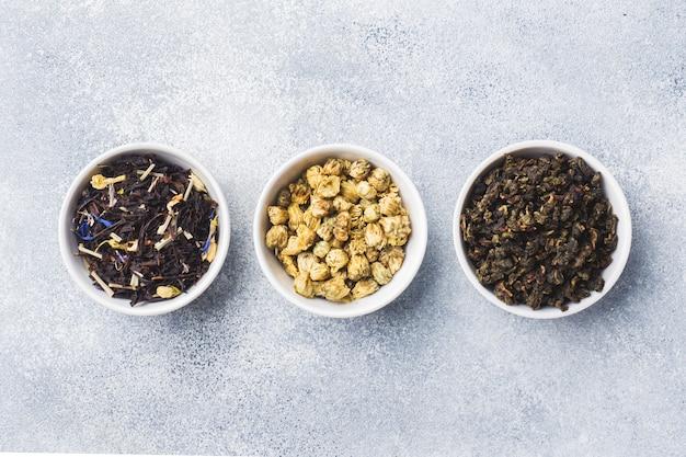 Variété de feuilles de thé séchées et de fleurs dans un bol sur fond gris.
