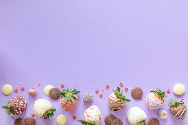 Variété de fraises enrobées de chocolat à la main avec différentes garnitures sur fond violet avec un espace libre pour le texte
