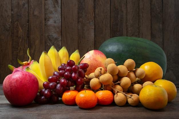Variété de fruits aux couleurs vives sur fond de bois ancien.