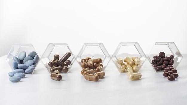 Variété de gélules et de comprimés médicaux renversés dans des bocaux hexagonaux en verre