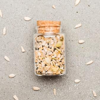 Variété de graines écrasées dans un petit pot en verre
