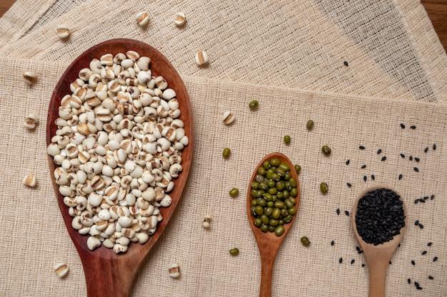 Variété de grains entiers, haricots verts, haricots rouges, millet dans une cuillère en bois, posée sur une nappe brune