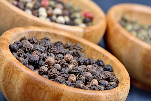 Variété de grains de poivre dans des bols en bambou