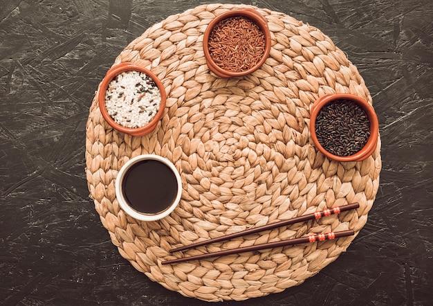 Variété de grains de riz dans trois bols sur le napperon circulaire avec des baguettes
