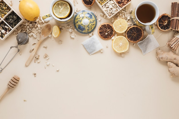 Variété d'herbes; cuillère; louche de miel; passoire à thé; fruits de raisin secs et ingrédients