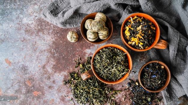 Variété d'herbes de thé dans la vue de dessus de bols
