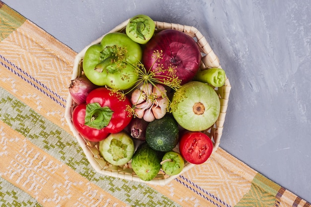 Variété de légumes dans un panier en bambou, vue du dessus.