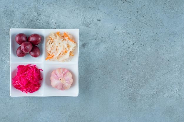Une variété de légumes fermentés dans une assiette , sur la table en marbre.